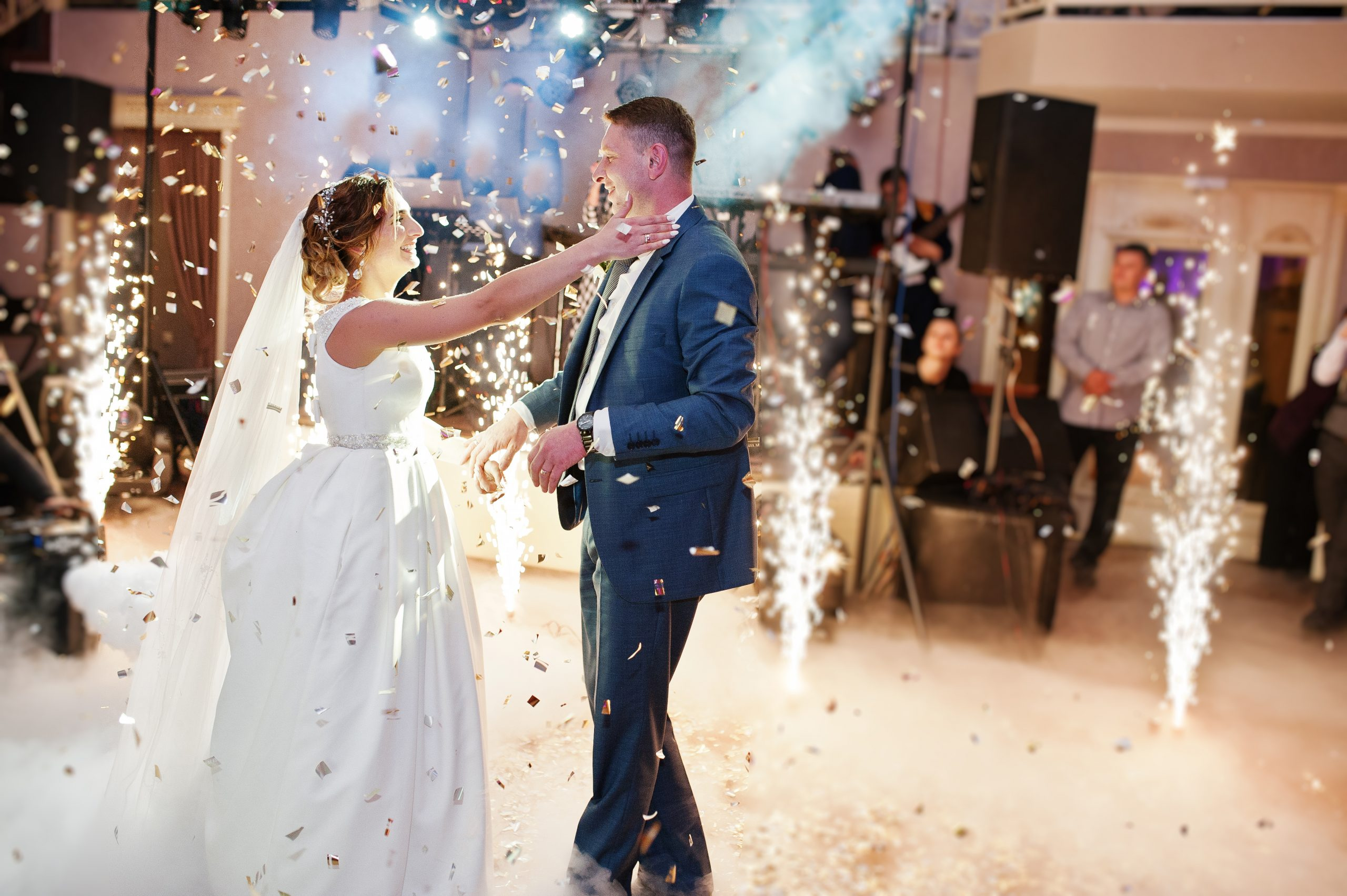 Newly married couple dancing on their wedding party with heavy smoke, multicolored lights and fireworks on the background.